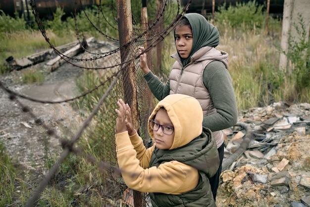 Deux petites filles en sweats à capuche et vestes debout près d'un camp de réfugiés divisant un filet