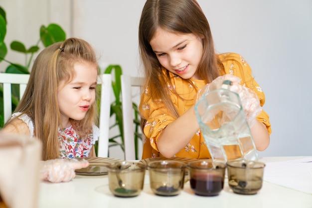 Deux petites filles versent de l'eau dans des verres avec de la peinture pour décorer des œufs. traditions familiales de pâques. créativité des enfants