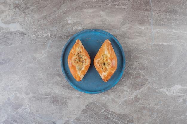 Deux petites portions de pide sur un plateau bleu sur une surface en marbre