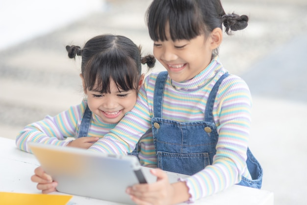 Deux petites soeurs asiatiques jouant avec une tablette numérique à la maison