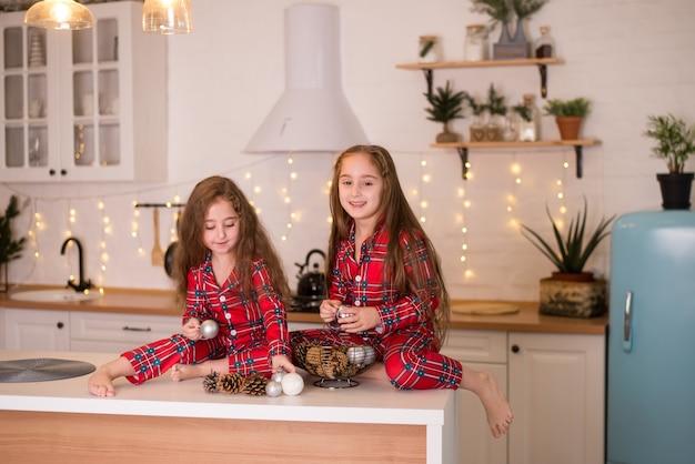 Deux petites soeurs charmantes dans le même pyjama rouge assis sur la table de la cuisine et jouant