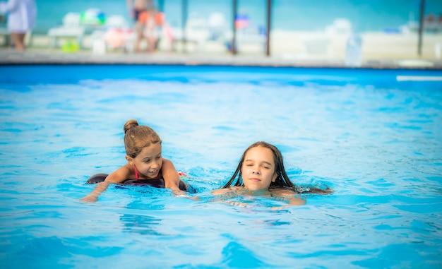 Deux petites sœurs filles nagent dans une grande piscine sur la plage