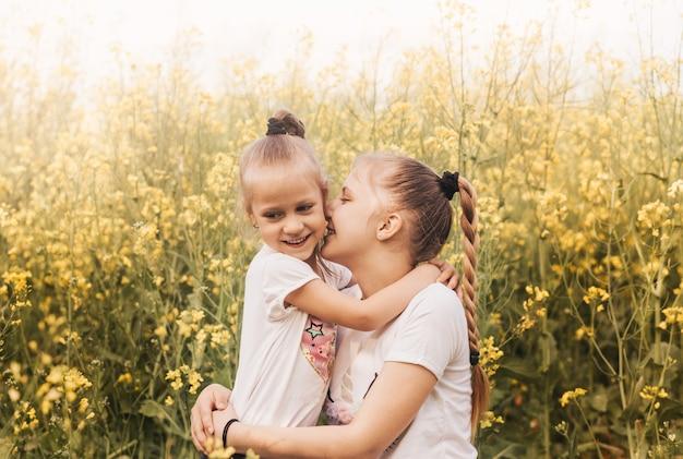 Deux petites sœurs filles se blottissent dans la nature en été