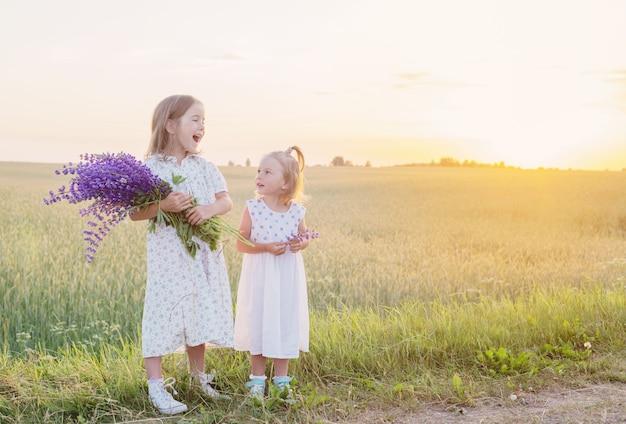 Deux petites soeurs avec des fleurs violettes en plein air