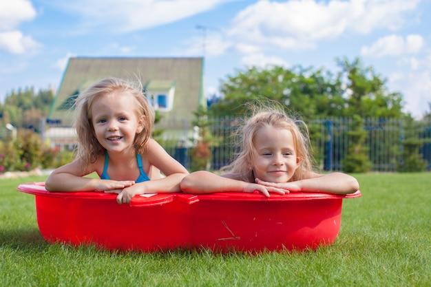 Deux petites soeurs gambadant et éclaboussant dans leur cour dans un petit bassin