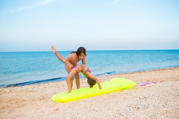 Deux petites sœurs gymnastes de petites filles positives font des exercices tout en vous relaxant sur une plage de sable par une chaude journée d'été ensoleillée