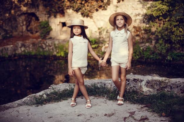 Deux petites sœurs heureuses aiment et s'embrassent dans un magnifique parc.