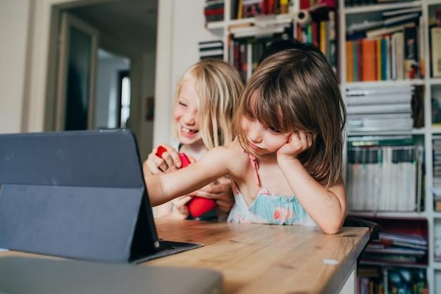 Deux petites soeurs à l'intérieur à la maison à l'aide de la table assise tablette