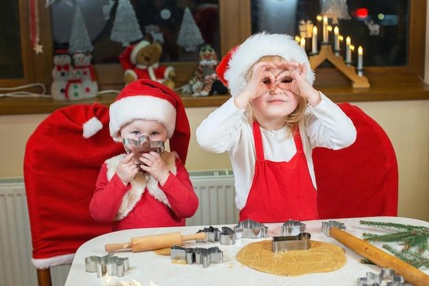 Deux petites soeurs mignonnes font cuire des biscuits de noël dans la cuisine à la maison confortable