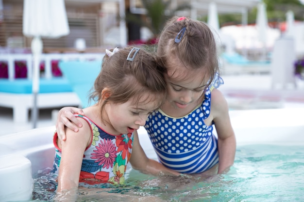 Deux petites sœurs mignonnes jouent dans la piscine. valeurs familiales et amitié.