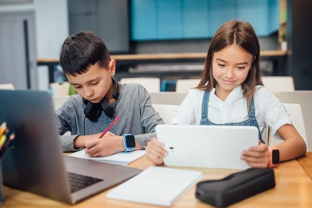 Deux petits amis écrivant leurs devoirs, utilisant une tablette numérique intelligente dans une salle de classe bleue moderne.