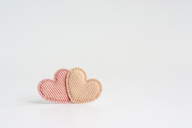 Deux petits coeurs textiles à rayures de couleur pastel se tiennent ensemble sur fond blanc
