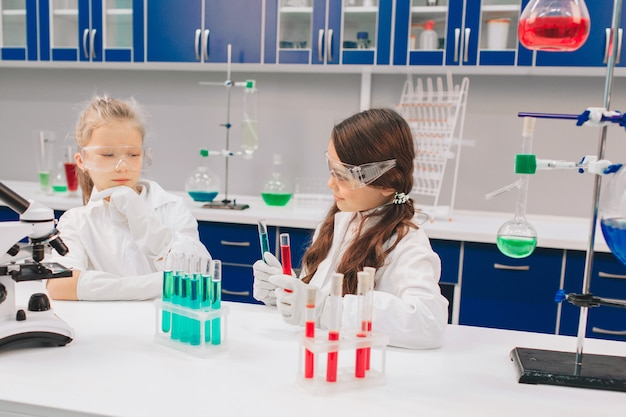 Deux petits enfants en blouse de laboratoire apprenant la chimie en laboratoire scolaire. jeunes scientifiques dans des lunettes de protection faisant l'expérience en laboratoire ou en armoire chimique. étudier les ingrédients pour les expériences.