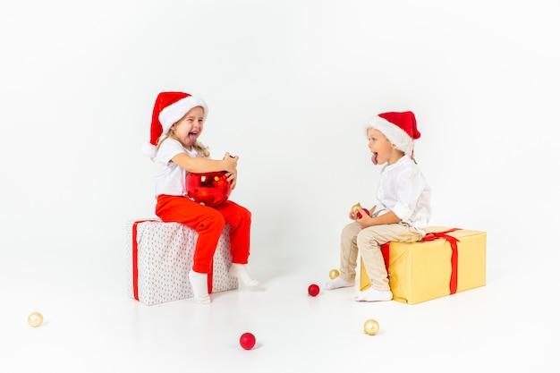 Deux petits enfants drôles en bonnet de noel assis sur des coffrets cadeaux. isolé sur fond blanc. concept de noël et du nouvel an.