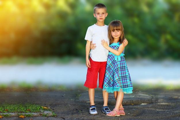 Deux petits enfants frère et sœur ensemble. fille en robe étreignant garçon. concept de relations familiales.
