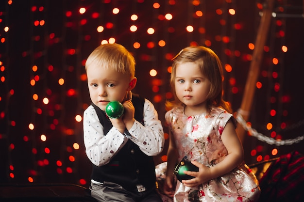 Deux petits enfants jouant avec des arcs de noël verts près de décoration et arbre de noël