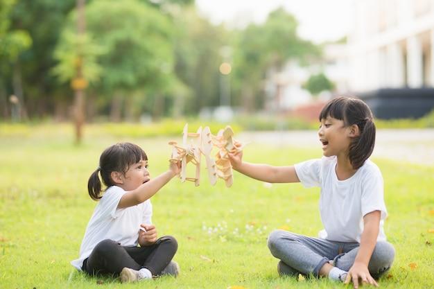 Deux petits enfants jouant avec un avion jouet en carton dans le parc pendant la journée