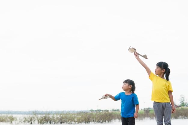 Deux petits enfants jouant avec un avion jouet en carton dans le parc pendant la journée.