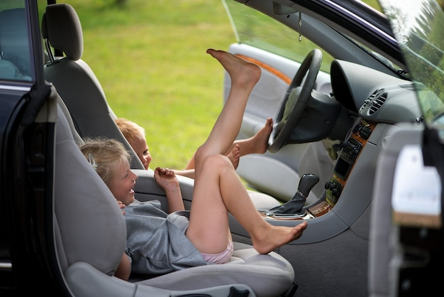 Deux petits enfants mignons - un frère et une sœur jouant à la conduite dans la voiture au volant.