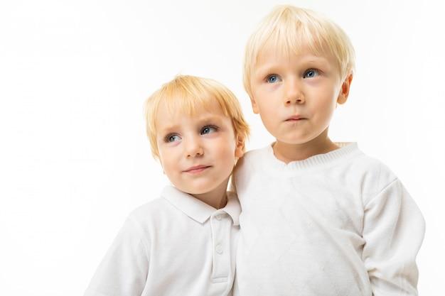 Deux petits frères caucasiens avec des sourires blonds et blonds, portrait isolé sur mur blanc