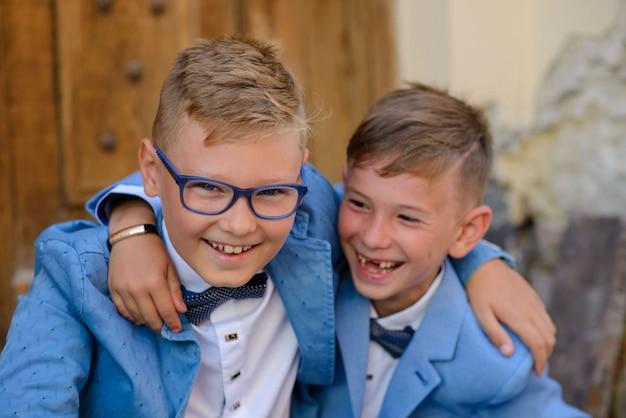 Deux petits frères en costume sont assis sur les marches et se serrent dans leurs bras. les enfants sourient. fermer.