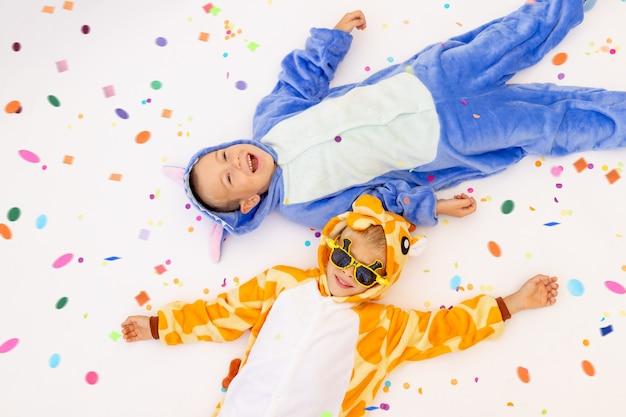 Deux petits frères garçons en costumes lumineux avec des confettis