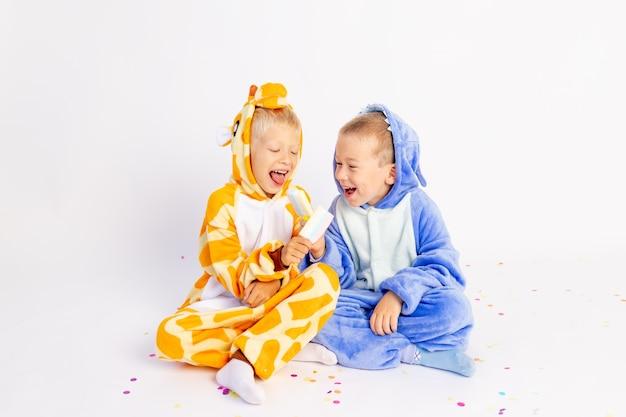 Deux petits frères garçons en costumes lumineux mangent de la glace et se livrent