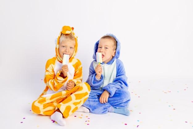 Deux petits frères garçons en costumes lumineux mangent de la glace