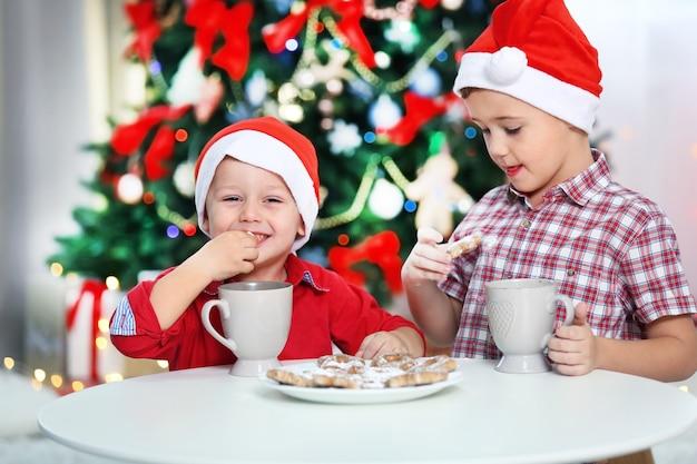 Deux petits frères mignons mangeant des biscuits sur le fond de décoration de noël