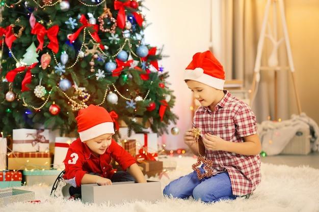 Deux petits frères mignons ouvrant des cadeaux sur la décoration de noël