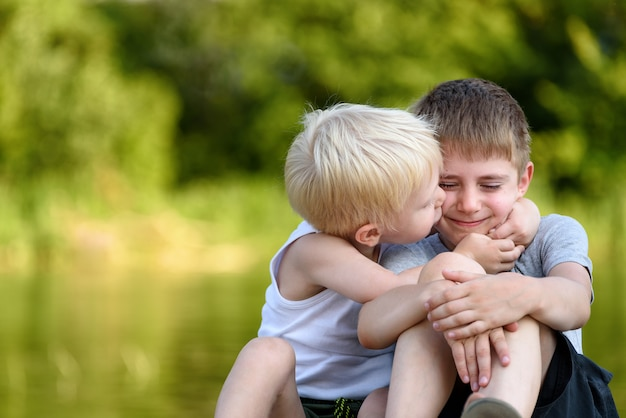 Deux petits frères sont assis à l'extérieur. l'un embrasse l'autre joue. arbres verts floues au loin. amitié et fraternité.