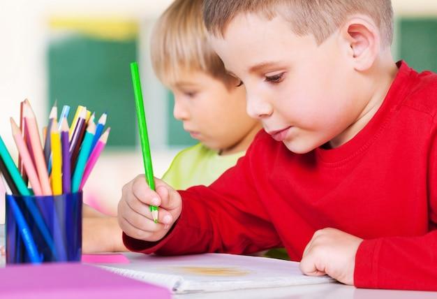 Deux petits garçons étudient le sujet sur fond
