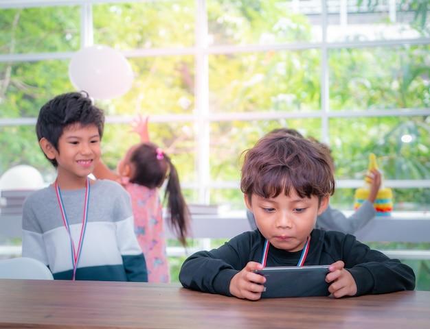 Deux petits garçons jouent à un jeu en ligne sur téléphone mobile