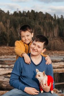 Deux petits garçons sont assis dans une étreinte sur des rondins au bord de la rivière dans les bras d'un chien chihuahua. le concept d'amitié et de fraternité. loisirs de plein air.