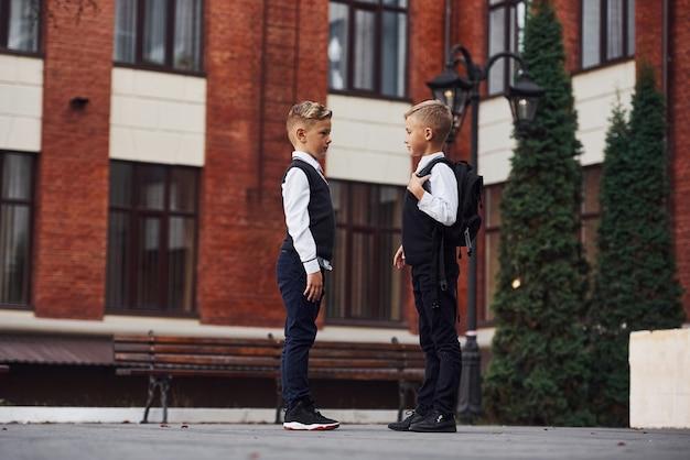 Deux petits garçons en uniforme scolaire qui sont ensemble à l'extérieur près du bâtiment de l'éducation.