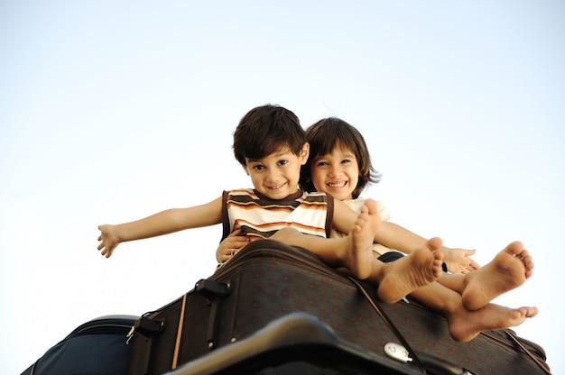 Deux petits garçons voyageant sur des sacs, le dessus de la voiture