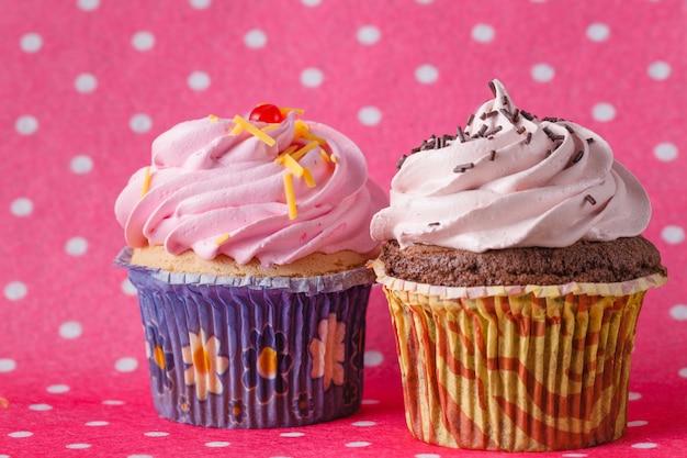 Deux petits gâteaux sur un espace rose coloré