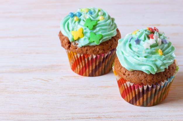 Deux petits gâteaux faits à la main colorés avec de la crème verte sur un fond en bois blanc.