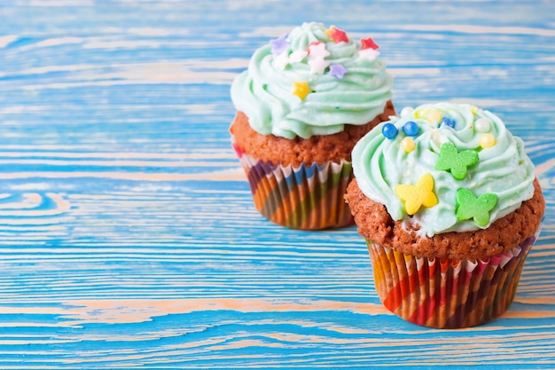 Deux petits gâteaux faits à la main colorés avec de la crème verte sur un fond en bois bleu.