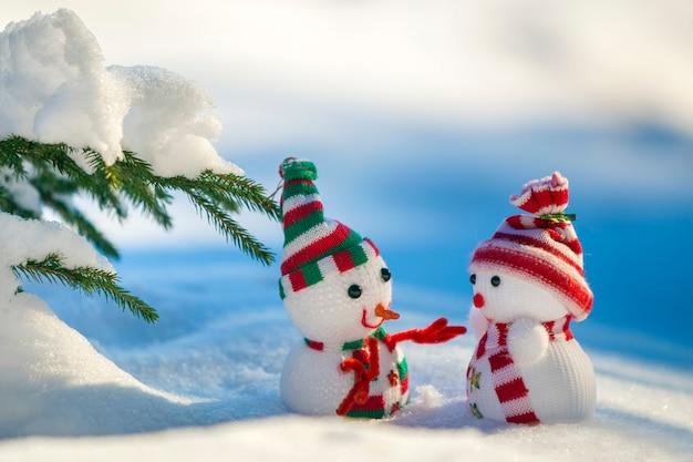 Deux petits jouets drôles bébé bonhomme de neige dans des chapeaux et des écharpes en tricot dans la neige profonde à l'extérieur sur bleu et blanc lumineux carte de voeux de bonne année et joyeux noël.
