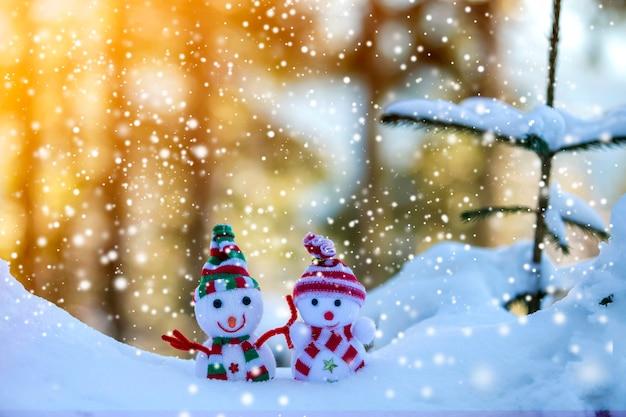 Deux petits jouets drôles bébé bonhomme de neige dans des chapeaux et des écharpes en tricot dans la neige profonde à l'extérieur près d'une branche de pin. carte de voeux de bonne année et joyeux noël.