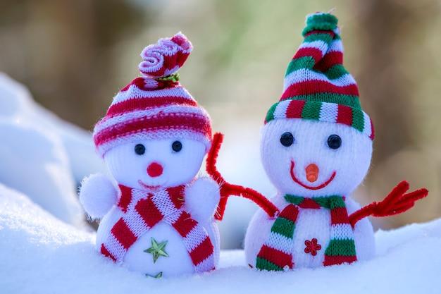 Deux petits jouets drôles bébé bonhomme de neige dans des chapeaux et des foulards tricotés dans la neige profonde à l'extérieur sur fond d'espace copie bleu et blanc lumineux. carte de voeux de bonne année et joyeux noël.