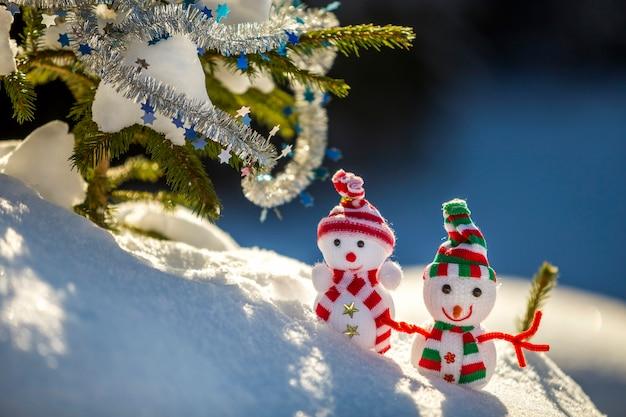 Deux petits jouets drôles bébé bonhomme de neige dans des chapeaux tricotés et des écharpes dans la neige profonde à l'extérieur près de la branche de pin. bonne année et carte de voeux joyeux noël.