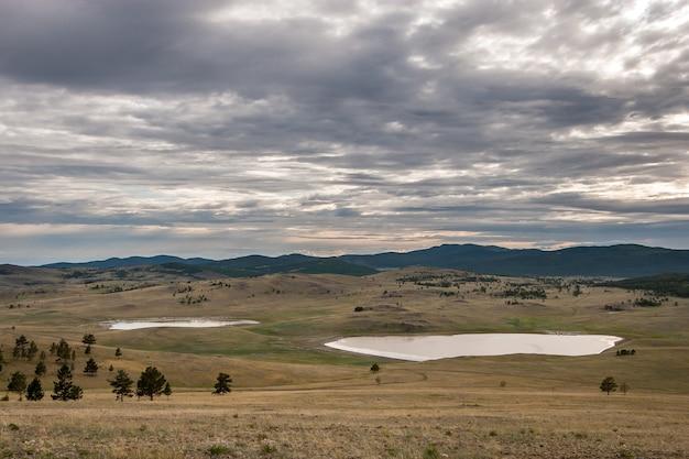 Deux petits lacs dans la steppe entre les collines. peu d'arbres bas. le ciel est couvert. horizontal.