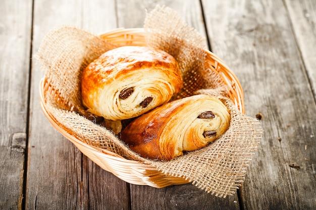 Deux petits pains au chocolat dans le panier allongé sur la vieille table en bois
