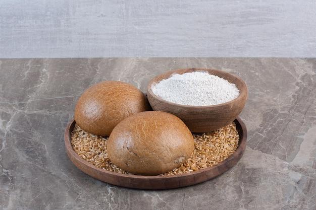 Deux petits pains et un bol de farine sur un plateau sur fond de marbre. photo de haute qualité