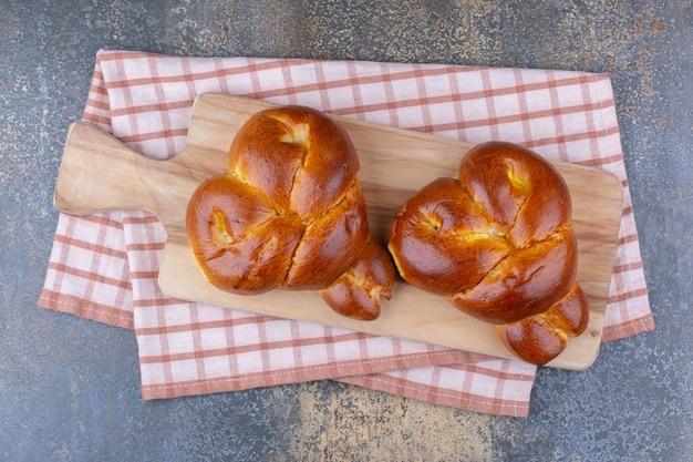 Deux petits pains en forme de coeur sur une planche sur une surface en marbre