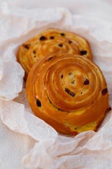 Deux petits pains frais aux raisins secs et crème de banane, sur papier sulfurisé