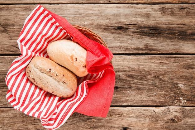 Deux petits pains frais dans le panier sur une table en bois, vue de dessus. surface des aliments