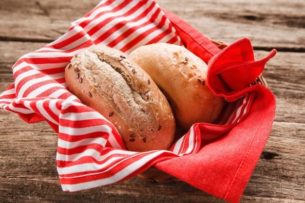 Deux petits pains frais dans le panier sur table en bois, vue rapprochée. surface des aliments